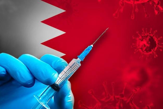 바레인 코비드19 예방 접종 캠페인 파란색 고무 장갑을 끼고 깃발 앞에 주사기를 들고 있습니다