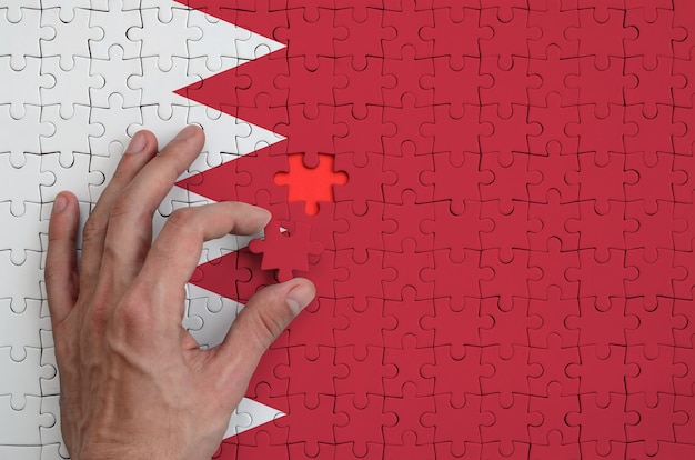 Bahrain flag is depicted on a puzzle, which the man's hand completes to fold