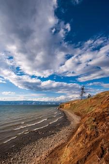 Берег озера байкал с горами на заднем плане, красивыми облаками и светом. камни у озера. горы в дымке. вертикальная рамка.