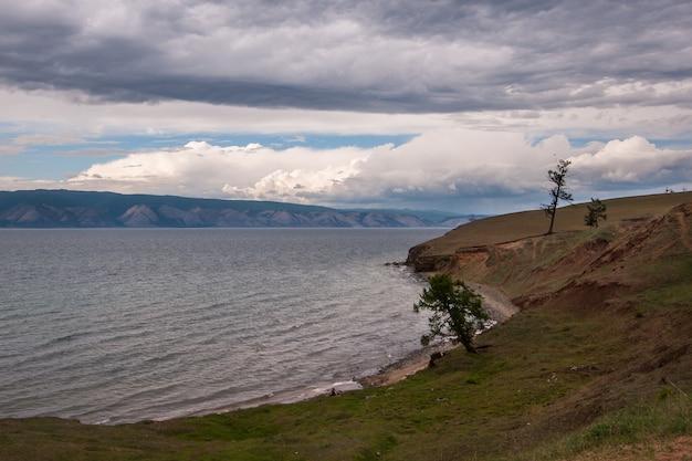 Берег озера байкал с горами на заднем плане и красивыми облаками. деревья на берегу озера. озеро с волнами.