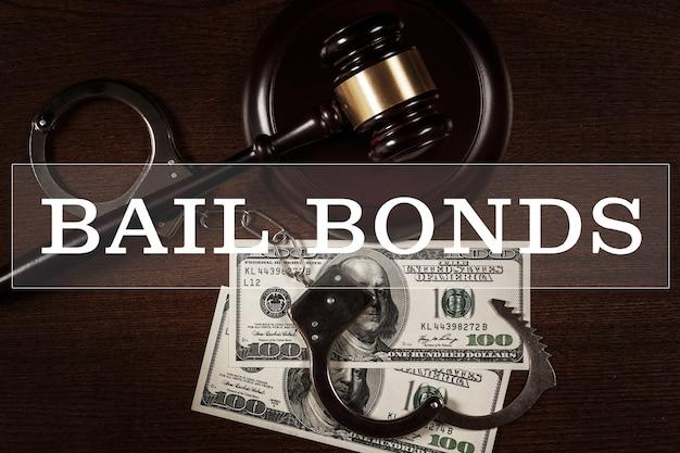 保釈保証サービスの概念。木製の背景にガベル、手錠、お金を判断します。