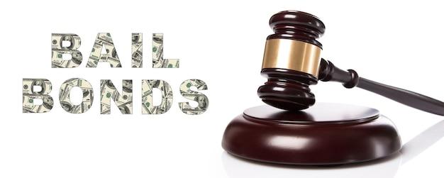 保釈保証サービスの概念。白い背景の上の裁判官のガベル。