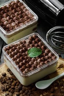 Тирамису бейлис с шариковыми крышками представлены в стеклянных коробках. сфотографировано в темной и винтажной концепции с украшением кофейного зерна.