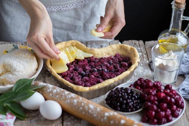 ハートの形をしたフルーツケーキを焼きます。おいしい自家製ケーキは自分で作ってください。料理。