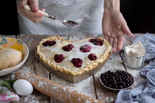 Выпекать фруктовый торт в форме. сахар, посыпанный фруктовым пирогом. мама готовит десерт. готовить дома.