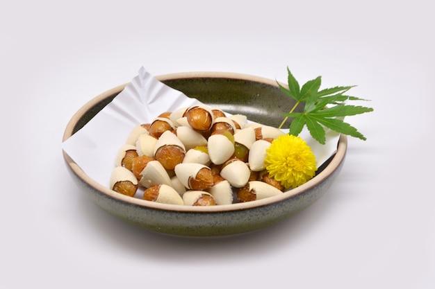 흰색 배경에 갈색 그릇 일본식 빵 은행 나무 (은행 나무 biloba) 소금