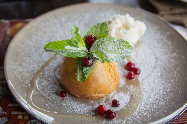 The baked apple with ice cream and mint on a ceramic plate.  useful dessert.