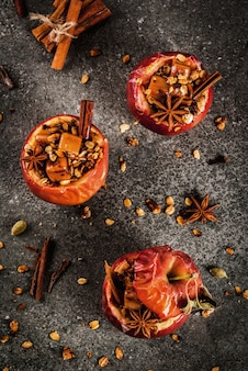 Baked apples stuffed with granola, toffee and spices on black stone table