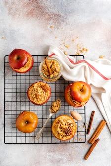 Запеченные яблоки, фаршированные орехами пекан, корицей, стрейзелем и медом на старом бетонном светлом фоне. деревенский несвежий