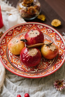 Baked apples with cottage cheese and cocoa on a beautiful red plate