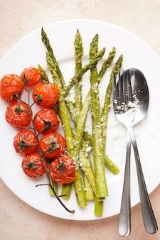 Запеченная спаржа и помидоры черри в тарелке на бежевом фоне, плоская планировка. вертикально.