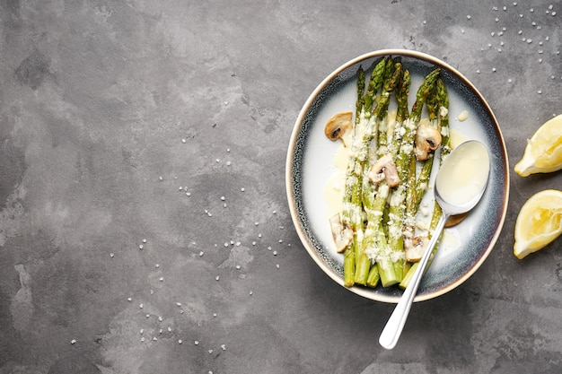 Запеченная спаржа и грибы с соусом в тарелке на сером фоне, место для текста. плоская планировка.