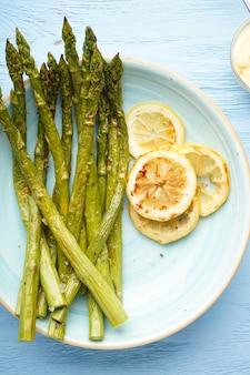 Запеченная спаржа с лимоном в тарелке на деревянном фоне. плоская планировка.
