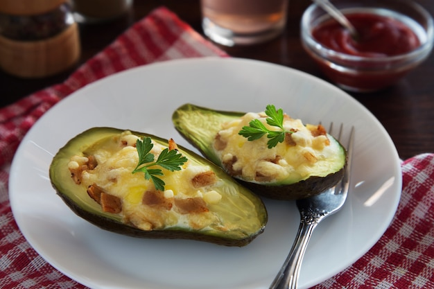 Baked avocado with cheese, parsley and bacon