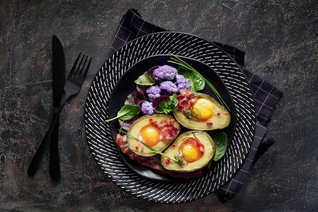 Baked avocado with egg and bacon ,flat lay on dark background