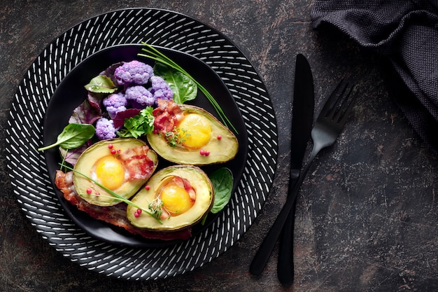 Baked avocado with egg and bacon flat lay on dark