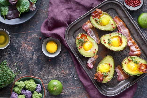 Baked avocado with egg and bacon on a metal baking tray, flat lay with ingredients and herbs on dark
