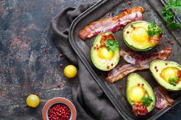 Baked avocado with egg and bacon on a metal baking tray, flat lay with ispices and herbs