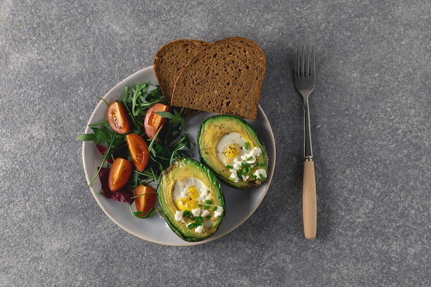 Baked avocado with quail eggs, arugula, cherry tomatoes, wholegrain bread, top view