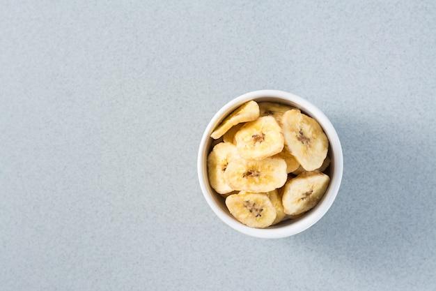 テーブルの上の白いボウルに焼きバナナチップ。ファストフード。スペースをコピーします。上面図