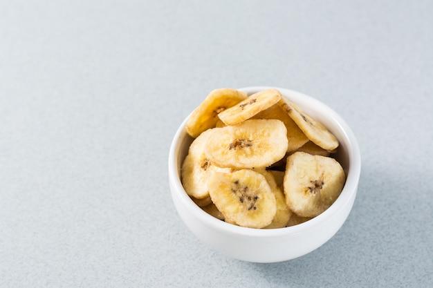 Запеченные банановые чипсы в белой миске на столе. быстрое питание. копировать пространство