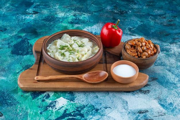 Запеченная фасоль, душбара, ложка, перец и соль на доске, на синем фоне.