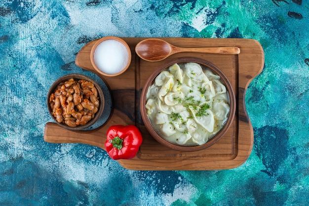 Запеченная фасоль, душбара, ложка, перец и соль на доске, на синем столе.