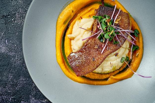 Запеченный говяжий язык с картофельным пюре и морковью в серой миске на черном фоне. вид сверху. закрыть вверх