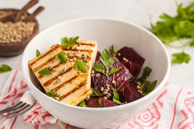 Baked beet salad with grilled tofu parsley and oil in a white bowl.
