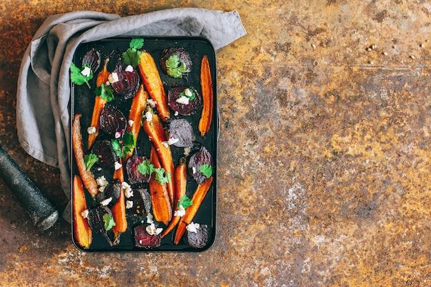 Запеченная свекла и морковь в старинной черной кастрюле с семенами укропа ricotta и свежей кориандром