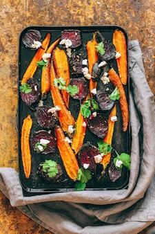 Запеченная свекла и морковь в старинной черной кастрюле с рикоттой на ржавом фоне.