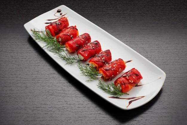 Запеченный болгарский перец в рулетах со сливочным сыром и укропом, на белой тарелке, на темном фоне