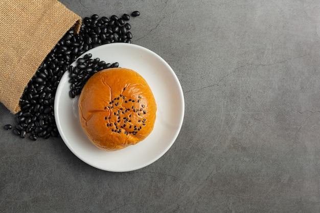 Panini di pasta di fagioli neri al forno sulla piastra bianca