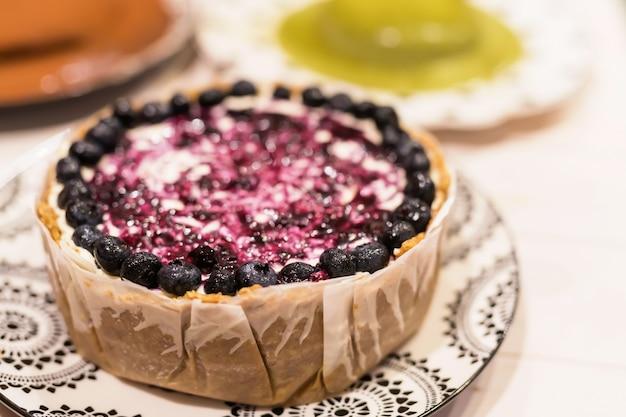 ブルーベリーチーズケーキを焼き、白い木製のテーブルに緑茶、チョコレートケーキをぼかします。夕食で祝う多くのバースデーケーキ。