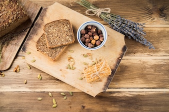 Baked bread and energy bar on chopping board over the table