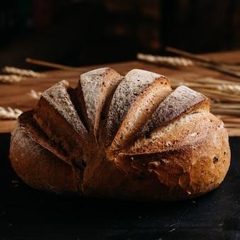 Pane cotto marrone intero su tessuto nero e marrone