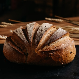 Испеченный хлеб весь коричневый на черной ткани и коричневый