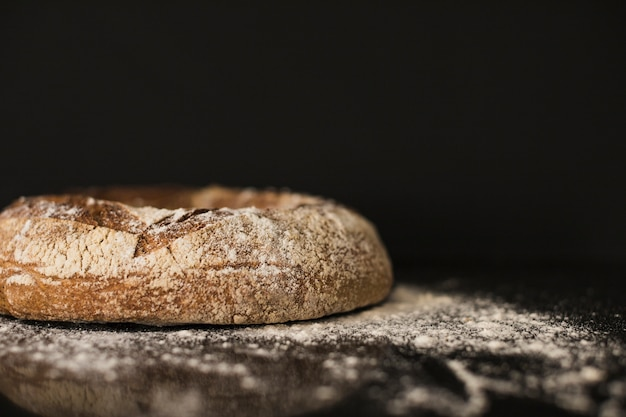 Baked bread bun dusted on flour against black background