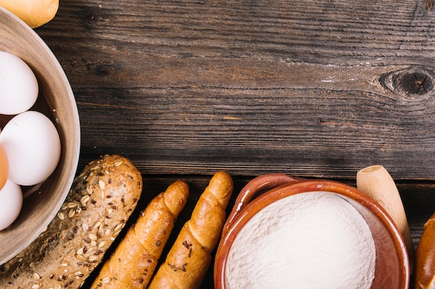 Baked bread; flour and eggs in bowl on wooden textured backdrop