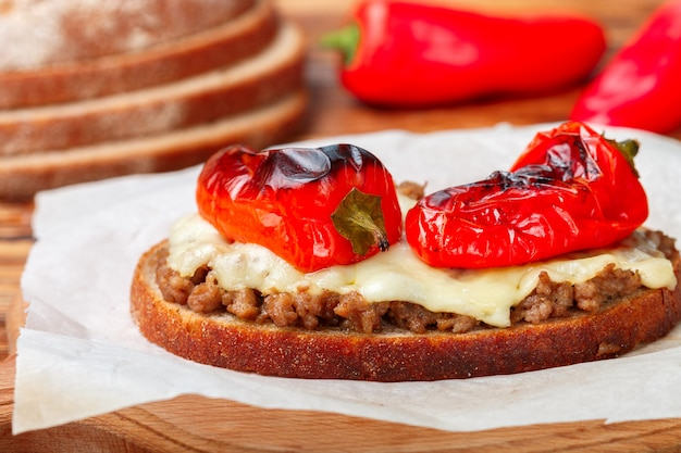 Baked bread toast with minced meat, cheese and red pepper