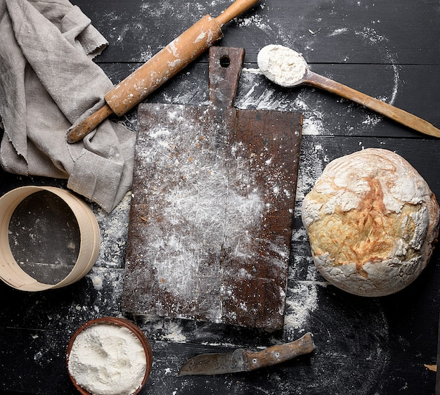 Baked bread, white wheat flour, wooden rolling pin and old cutting board