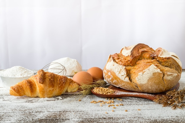 Baked bread with cereals placed on a wooden table.
