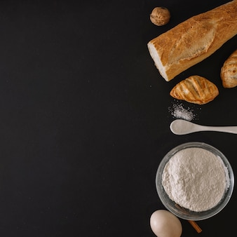 Baked breads; flour; egg and walnut on black background