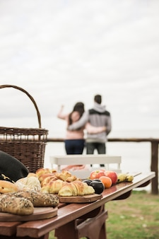 Baked breads and fruits on wooden table and couple at background