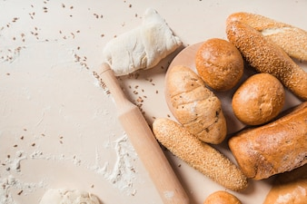 Baked breads with dough and rolling pin on backdrop