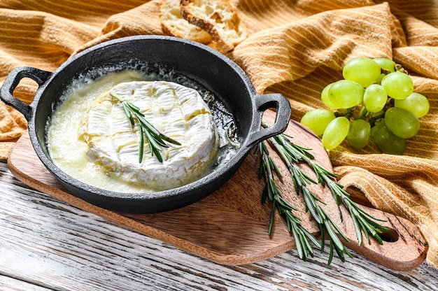 Baked brie cheese, camembert with rosemary in a pan. white wooden background. top view