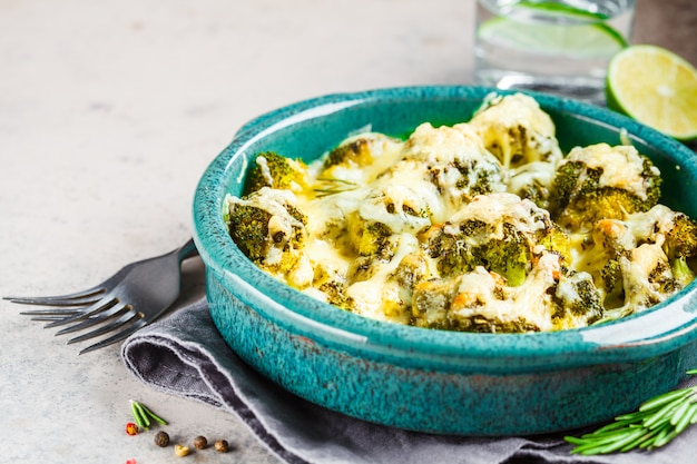 Baked broccoli casserole with cheese in blue dish, gray background. vegetarian food concept.