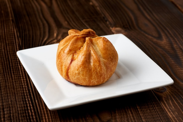 Baked bun on plate on a wooden table