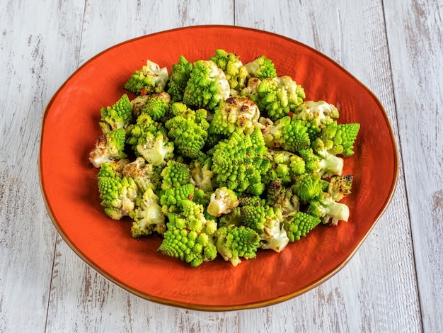 Baked cabbage romanesco with spices on a orange plate