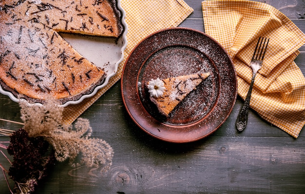 Baked cake in a ceramic form sprinkled with chocolate slices on a wooden table.  slice of cake laid on clay plate and decorated with flower